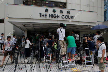 """Members of press wait outside the High Court in Hong Kong, . The former lover of quirky billionaire Nina Wang has been sentenced to 12 years in prison after a Hong Kong court found him guilty of forging her will to claim her multibillion-dollar estate. The Court judge on Friday called Peter Chan, formerly known as Tony Chan, """"shameless"""" and """"wicked"""" for taking advantage of Wang's trust in him. Chan is a former feng shui master who changed his name from Tony after converting recently to Christianity"""