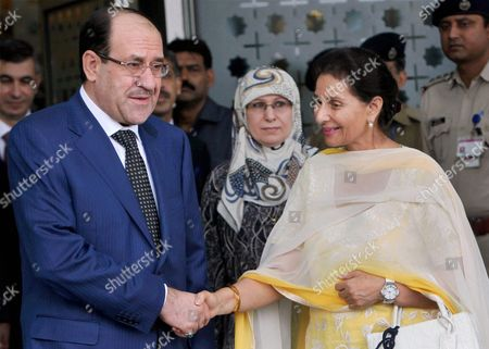 Indian Junior Foreign Minister Preneet Kaur shakes hand with Iraqi Prime Minister Nouri Kamil Al-Maliki, left, upon his arrival in New Delhi, India, . Al-Maliki is on a four-day visit to India