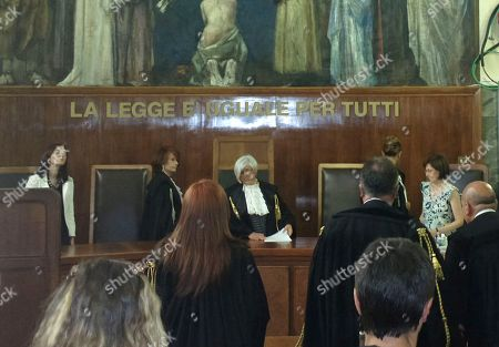 "Judge Anna Maria Gatto, center, reads the sentence at the Milan court, Italy, . A Milan court on Friday, July 19, 2013 convicted three of ex-premier Silvio Berlusconi's former aides of procuring prostitutes for the media mogul's infamous ""bunga bunga"" parties. The court also handed down stiff prison terms: seven years to Emilio Fede, a longtime executive in the mogul's TV networks; seven years to Dario ""Lele"" Mora, a talent agent, and five years to Nicole Minetti, a former regional politician who professed love for the ex-premier. Berlusconi wasn't on trial in this case, but he was convicted separately last month of paying for sex with a minor and trying to cover it up. Both he and the young woman, a Moroccan who goes by her stage name ""Ruby,"" had denied having sex"