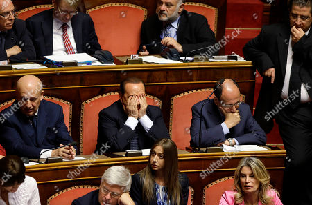 Former Italian Premier Silvio Berlusconi, center, attends a Senate session in Rome where his top aide, Interior Minister Angelino Alfano, faces a vote of non-confidence, . A judge in Naples will evaluate Friday the possible indictment of Berlusconi on charges of corruption for allegedly having paid a rival lawmaker to join his party. Meanwhile a court in Milan is expected later today to reach a verdict in a trial which sees three former Berlusconi aides, Nicole Minetti, Lele Mora and Emilio Fede, accused of procuring women as prostitutes for parties at the then-premier's villa near Milan