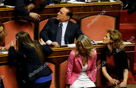 Former Italian Premier Silvio Berlusconi attends a Senate session in Rome where his top aide, Interior Minister Angelino Alfano, faces a vote of non-confidence, . A judge in Naples will evaluate Friday the possible indictment of Berlusconi on charges of corruption for allegedly having paid a rival lawmaker to join his party. Meanwhile a court in Milan is expected later today to reach a verdict in a trial which sees three former Berlusconi aides, Nicole Minetti, Lele Mora and Emilio Fede, accused of procuring women as prostitutes for parties at the then-premier's villa near Milan