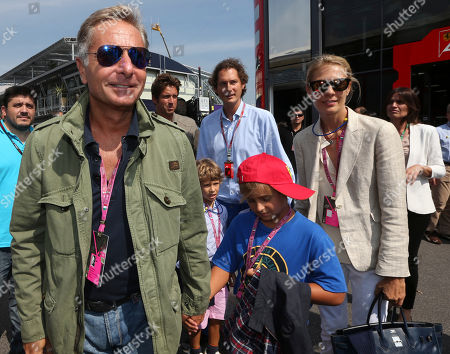 From left, Italian TV presenter Paolo Bonolis, Fiat president John Elkann and his wife Lavinia Borromeo attend the qualifying session in the paddock for the Italian Formula One Grand Prix at the Monza racetrack, in Monza, Italy, Saturday, Sept. 7, 2013. The Formula one race will be held on Sunday