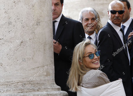 """Sharon Stone Actress Sharon Stone turns around to smile to photographers as she gets ready for a shoot in the movie """"Un ragazzo d'oro"""", by Italian director Pupi Avati, outside Rome's Santa Maria dei Miracoli Church"""