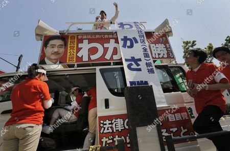 Upper House candidate Masaru Wakasa of the ruling Liberal Democratic Party (LDP) delivers his speech from the top of his vehicle during an election campaign in Tokyo, . Prime Minister Shinzo Abe's LDP and its junior partner, the New Komeito, are expected to gain a majority of the 242 seats in the less powerful upper house in the July 21 election. That would give them control of both houses of parliament, making it easier to pass legislation