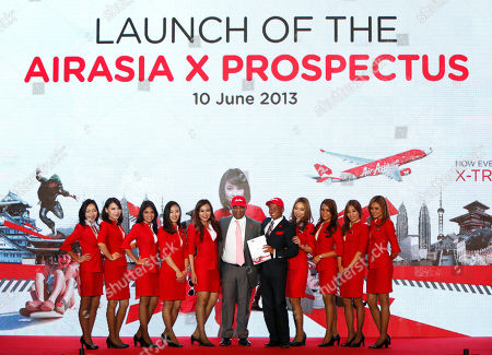 Tony Fernandes, Azran Osman-Rani AirAsia X Chief Executive Azran Osman-Rani, fifth from right, holds a newly launched AirAsia X prospectus as he poses with AirAsia Group Chief Executive Tony Fernandes, center, for photographers during its launch in Kuala Lumpur, Malaysia, . Malaysia's long-haul budget carrier AirAsia X said Monday it hopes to raise up to $275 million in the country's biggest share sale this year to repay debts and fund its expansion