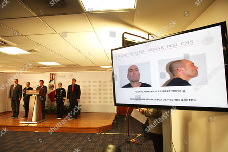 A mugshot of the top leader of Mexico's Gulf Cartel Mario Armando Ramirez Trevino is shown on a TV screen as Mexico's government spokesman Eduardo Sanchez, third from left, speaks during a news conference in Mexico City, . Mario Armando Ramirez Trevino, a top leader of Mexico's Gulf Cartel, was detained on Saturday Aug. 17, in a military operation near the Texas border, just weeks after the arrest of the leader of the brutal Zetas cartel near another border city, Nuevo Laredo