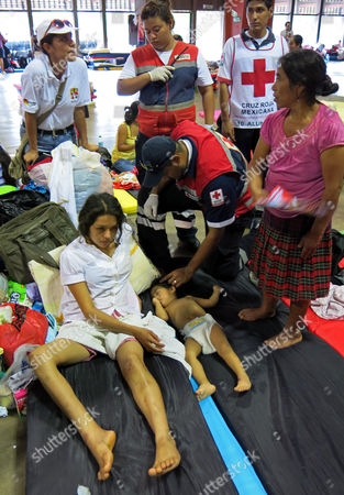 Nancy Gomez, 21, an injured resident of La Pintada, and her 1-year-old baby, receive medical attention in a shelter at the Convention Center in Acapulco, Mexico, . Federal police rescued more than 300 people from La Pintada after it was hit by a landslide Monday afternoon, but officials said at least 58 people were missing and presumed dead. Gomez said that she heard a strange sound and went to look out the doorway of her family's house, her baby clutched in her arms. She saw the ground move, then felt a jolt from behind as her father tried to push her to safety. She never saw him again