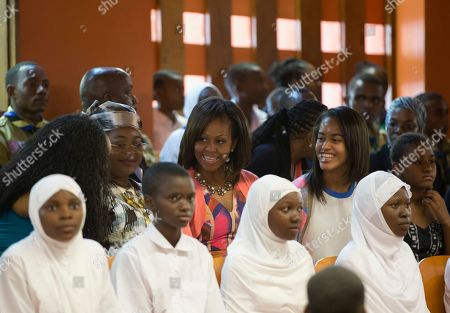 Michelle Obama, Salma Kikwete, Milia Obama, Sasha Obama First lady Michelle Obama, center, and her daughters Malia, second from right, and Sasha, right, sit among youths as they attend a performance by the Baba wa Watoto troupe with Tanzanian first lady Salma Kikwete, second from left, at the Baba wa Watoto Center in Dar es Salaam, Tanzania. The Baba wa Watoto Center serves underprivileged boys and girls between the ages of five and 18 years old
