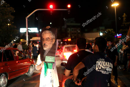 Stock Picture of A supporter of Iranian presidential candidate Hasan Rouhani holds up a poster of Green Movement leader Mir Hossein Mousavi, who was a candidate in 2009 and is currently under house arrest, while celebrating Rouhani's victory, in Tehran, Iran, . Wild celebrations broke out on Tehran streets that were battlefields four years ago as reformist-backed Rouhani capped a stunning surge to claim Iran's presidency on Saturday, throwing open the political order after relentless crackdowns by hard-liners to consolidate and safeguard their grip on power