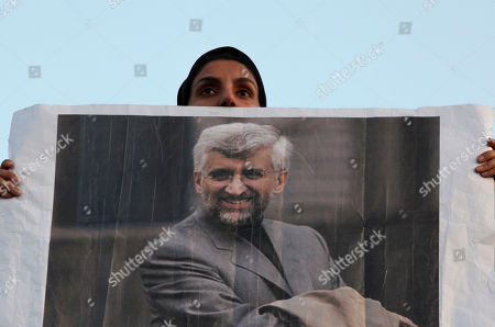 A female supporter of the Iranian presidential candidate Saeed Jalili, Iran's top nuclear negotiator, holds up his poster, in a campaign rally, two days prior to the election, in Tehran, Iran