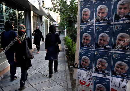 Iranian women walk past posters of presidential candidate Saeed Jalili, Iran's top nuclear negotiator, a day prior to the election, in Tehran, Iran, . Iran's presidential election on Friday may be defined by who doesn't vote. Liberal-leaning Iranians debated whether to stay away in silent protest or support the lone relatively moderate candidate and indirectly endorse what they claim is an undemocratic system