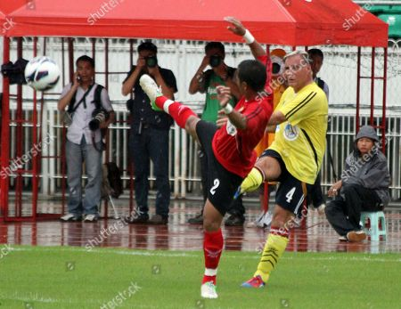 Former Manchester United player Clayton Blackmore, right, fights for the ball with Myanmar player Min Thu during their charity match at Thuwunna stadium in Yangon, Myanmar
