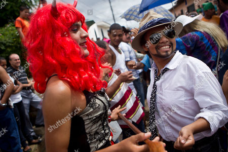 """A woman dressed as a man, right, dances with a man dressed as a woman during """"El Cartel"""" as part of celebrations honoring Santa Ana, or Saint Anne, the mother of the Virgin Mary, in Nandaime, Nicaragua. The celebration's unusual twist is the """"El Cartel"""" dance, where the boys and men of Nandaime show up wearing women's clothes and makeup. This year, at least one young woman came as a man, complete with tie, hat and painted on beard"""