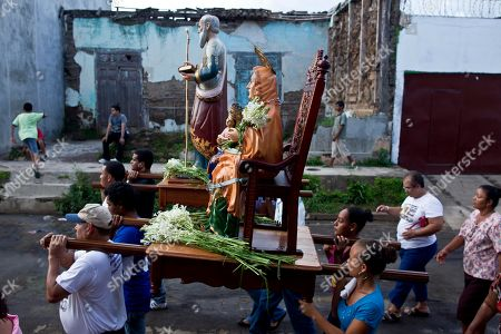 Catholics carry statues of Santa Ana, or Saint Anne, holding baby Mary, and Saint Anne's husband Joaquin, behind, in Nandaime, Nicaragua. Nandaime puts on a big show for two weeks every year to honor its patron saint, Santa Ana, the mother of the Virgin Mary