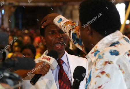 """T.B. Joshua T.B. Joshua lays his hand on the head of a worshipper during a service at the Synagogue, Church of All Nations, in Lagos Nigeria. T.B. Joshua's Synagogue, Church of All Nations has branches around the world, and a recent YouTube video even credits him with predicting the disappearance of Malaysian Airlines Flight MH370. Joshua is one of the best-known preachers in Africa and among the most profitable in Nigeria, the go-to faith healer and spiritual guide for leaders such as the late Ghanaian president John Atta Mills, Malawian president Joyce Banda and former Zimbabwean prime minister Morgan Tsvangirai. The man who says he comes from the poor village of Arigidi is worth between $10 and $15 million based on assets, according to Forbes magazine, which in 2011 estimated his personal wealth. The church holds some 15,000 people with outside tents for the overflow and Sunday services are beamed worldwide. Yet critics say this wildly popular televangelist hinders efforts to curtail the spread of HIV and tuberculosis with testimonies by church-goers that faith and his holy water can cure both. He is also accused of taking advantage of his followers and tightly controlling those closest to him, who call him """"Daddy"""