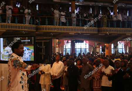 """T.B. Joshua T.B. Joshua conducts a service at the Synagogue, Church of All Nations, in Lagos Nigeria. T.B. Joshua's Synagogue, Church of All Nations has branches around the world, and a recent YouTube video even credits him with predicting the disappearance of Malaysian Airlines Flight MH370. Joshua is one of the best-known preachers in Africa and among the most profitable in Nigeria, the go-to faith healer and spiritual guide for leaders such as the late Ghanaian president John Atta Mills, Malawian president Joyce Banda and former Zimbabwean prime minister Morgan Tsvangirai. The man who says he comes from the poor village of Arigidi is worth between $10 and $15 million based on assets, according to Forbes magazine, which in 2011 estimated his personal wealth. The church holds some 15,000 people with outside tents for the overflow and Sunday services are beamed worldwide. Yet critics say this wildly popular televangelist hinders efforts to curtail the spread of HIV and tuberculosis with testimonies by church-goers that faith and his holy water can cure both. He is also accused of taking advantage of his followers and tightly controlling those closest to him, who call him """"Daddy"""