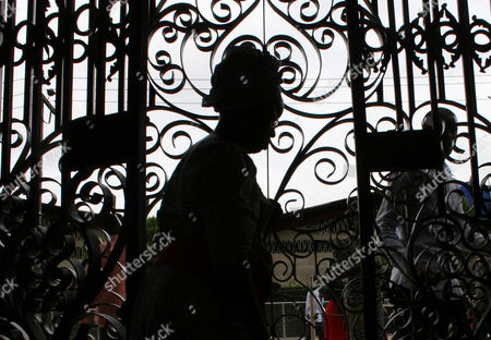 """A worshipper passes a wrought iron gate outside the The Synagogue, Church Of All Nations in Lagos Nigeria. T.B. Joshua's Synagogue, Church of All Nations has branches around the world, and a recent YouTube video even credits him with predicting the disappearance of Malaysian Airlines Flight MH370. Joshua is one of the best-known preachers in Africa and among the most profitable in Nigeria, the go-to faith healer and spiritual guide for leaders such as the late Ghanaian president John Atta Mills, Malawian president Joyce Banda and former Zimbabwean prime minister Morgan Tsvangirai. The man who says he comes from the poor village of Arigidi is worth between $10 and $15 million based on assets, according to Forbes magazine, which in 2011 estimated his personal wealth. The church holds some 15,000 people with outside tents for the overflow and Sunday services are beamed worldwide. Yet critics say this wildly popular televangelist hinders efforts to curtail the spread of HIV and tuberculosis with testimonies by church-goers that faith and his holy water can cure both. He is also accused of taking advantage of his followers and tightly controlling those closest to him, who call him """"Daddy"""