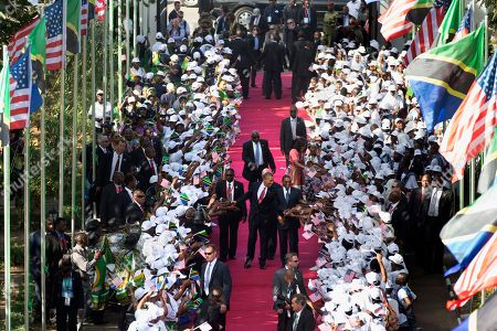 Michelle Obama, Salma Kikwete, Jakaya Kikwete, Barack Obama President Barack Obama and Tanzanian President Jakaya Kikwete walk in front of first lady Michelle Obama and Tanzanian first lady Salma Kikwete greeting the cheering crowd as they arrive at the State House in Dar es Salaam, Tanzania