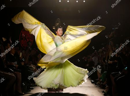 Chinese singer Li Yugang performs and wears a creation by Chinese fashion designer Lawrence Xu during her Women's Fall Winter 2013 haute couture fashion collection in Paris, France