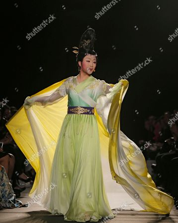 Stock Image of Chinese's Tenor Li Yugang of Beijing performs and wears a creation by Chinese fashion designer Lawrence Xu during her Women's Fall Winter 2013 haute couture fashion collection in Paris, France