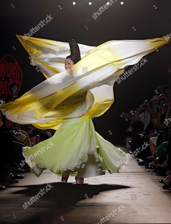 Stock Picture of Chinese singer Li Yugang performs and wears a creation by Chinese fashion designer Laurence Xu during her Women's Fall Winter 2013 haute couture fashion collection in Paris, France