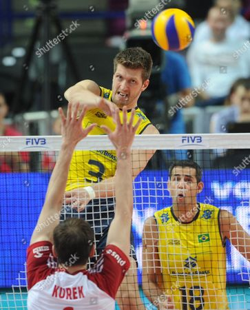 Carbonera Eder, Bartosz Kurek, Amaral Dante Brazil's Carbonera Eder spikes the ball against Poland's Bartosz Kurek, as Brazil's Amaral Dante, right, watches the action, during their World League Pool A game in Warsaw, Poland