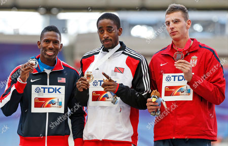 From left, United States' Michael Tinsley, Trinidad and Tobago's Jehue Gordon and Serbia's Emir Bekric pose on the podium during the medal ceremony for the men's 400-meter hurdles at the World Athletics Championships in the Luzhniki stadium in Moscow, Russia, . Gordon won gold, Tinsley silver and Bekric bronze