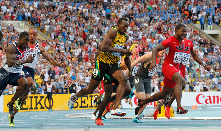 Jamaica's Usain Bolt, center, receives the baton ahead of United States' Justin Gatlin, right, and Britain's Dwayne Chambers, left, in the men's 4x100-meter relay final at the World Athletics Championships in the Luzhniki stadium in Moscow, Russia