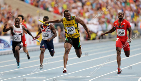 Jamaica's Usain Bolt, second from right, crosses the finish line to win ahead of United States' Justin Gatlin, right, and Britain's Dwayne Chambers, second from left, in the men's 4x100-meter relay final at the World Athletics Championships in the Luzhniki stadium in Moscow, Russia