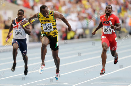 Jamaica's Usain Bolt, center, crosses the finish line to win ahead of United States' Justin Gatlin, right, and Britain's Dwayne Chambers in the men's 4x100-meter relay final at the World Athletics Championships in the Luzhniki stadium in Moscow, Russia
