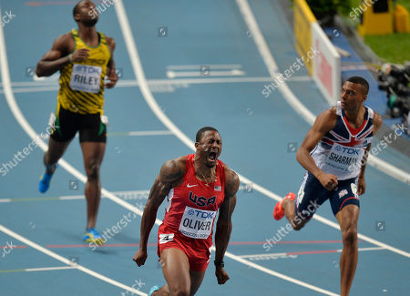 United States' David Oliver, center, reacts as he crosses the finish line to win gold ahead of Britain's William Sharman in the men's 110-meter hurdles final at the World Athletics Championships in the Luzhniki stadium in Moscow, Russia