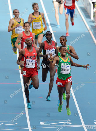 Ethiopia's Hagos Gebrhiwet, front right, crosses ahead of United States' Bernard Lagat, front left, as they compete in a men's 5000-meter heat at the World Athletics Championships in the Luzhniki stadium in Moscow, Russia