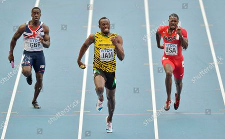 Jamaica's Usain Bolt, center, competes to win ahead of United States' Justin Gatlin, right, and Britain's Dwayne Chambers in the men's 4x100-meter relay final at the World Athletics Championships in the Luzhniki stadium in Moscow, Russia
