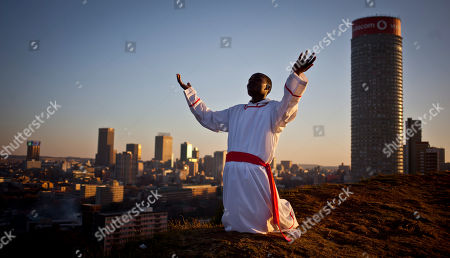 A worshipper prays to God at sunset asking that he will be accepted into heaven, on a hilltop overlooking Johannesburg, South Africa . Nelson Mandela's wife, Graca Machel, said Friday that she is less anxious because the 94-year-old anti-apartheid leader and former South African president is responding to treatment