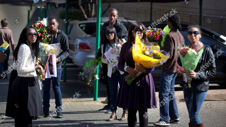 Ndileka Mandela Granddaughter Ndileka Mandela, center right, with other relatives carry bunches of flowers that were left by wellwishers into the Mediclinic Heart Hospital where former South African President Nelson Mandela is being treated in Pretoria, South Africa . President Jacob Zuma canceled a trip to Mozambique on Thursday in an indication of heightened concern about Mandela, whose health deteriorated last weekend