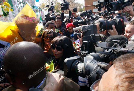 Stock Photo of Nelson Mandela Granddaughters Zaziwe Dlamini-Manaway, center, and Tukwini Mandela, center left, are swamped by the media after collecting flowers from wellwishers outside the Mediclinic Heart Hospital where former South African President Nelson Mandela is being treated in Pretoria, South Africa . President Jacob Zuma canceled a trip to Mozambique on Thursday in an indication of heightened concern about Mandela, whose health deteriorated last weekend
