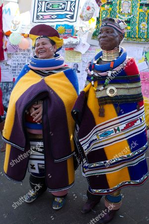 Esther Mahlangu, a contemporary South African artist, right, with Nothembi Mkhwebane, a musician, left, stand outside the Mediclinic Heart Hospital where former South African President Nelson Mandela is being treated in Pretoria, South Africa