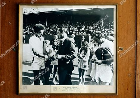 """A framed photograph dated 1973, of US tennis player Arthur Ashe, left, shaking hands with Ken William of South African Breweries, center, as Tom Okker, a Dutch, right, tennis player looking on after winning their final at the Ellis Park tennis stadium in Johannesburg, South Africa, . The gold paint on the winners' boards at the Ellis Park tennis stadium sparkles with names of past tennis greats like Rod Laver, Jimmy Connors, Margaret Court, Billie Jean King and many more, yet an air of neglect now cloaks the clubhouse, and dust coats the counter of """"The Tennis Bar"""". Ellis Park was once the temple of South African tennis under white minority rule, with a celebrity-studded list of players on the international circuit, but now it struggles for funding and the once thriving tennis centre now only echoes with the sound of past glories"""