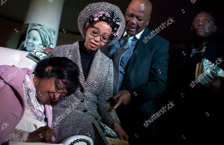 """Winnie Madikizela-Mandela Winnie Madikizela-Mandela, left, signs a copy of her book for Justice Minister Jeff Radebe, second from right, and his wife Bridgette Radebe, second from left, during her book launch at the Constitution Hill in Johannesburg, South Africa, . Mandela, an Apartheid-era struggle stalwart, was joined by family and friends at a former women's prison in Johannesburg's Constitutional Hill to launch """"491 days"""" - an account of her arrest and imprisonment in solitary confinement"""
