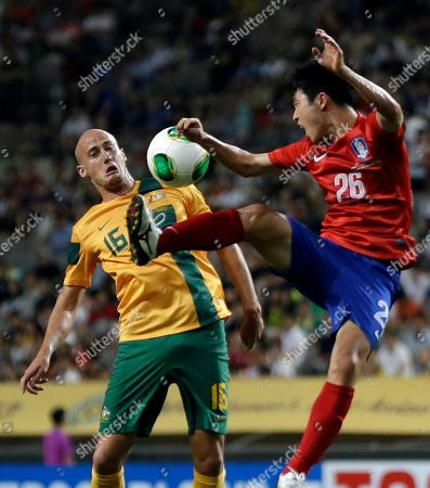 South Korea's Lee Seung-gi, right, fights for the ball against Australia's Ruben A. Zadkovic during their East Asian Cup soccer match at Seoul World Cup stadium in Seoul, South Korea