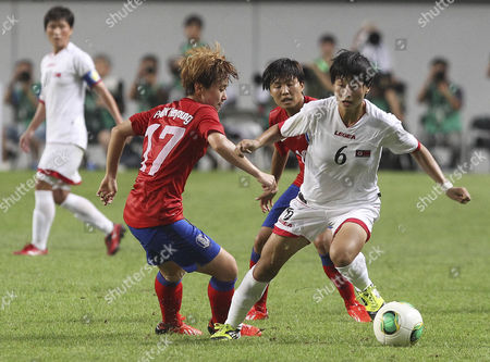 Kim Un Hyang, Ji So-yun, Park Hee-young North Korea's Kim Un Hyang, right, fights for the ball against South Korea's Ji So-yun, center, and Park Hee-young, left, during their Women's East Asian Cup soccer match at Seoul World Cup stadium in Seoul, South Korea