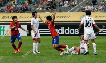 South Korea's Kim Soo-yun, center, celebrates her goal with Ji So-yun, left, in a match against North Korea during their Women's East Asian Cup soccer at Seoul World Cup stadium in Seoul, South Korea