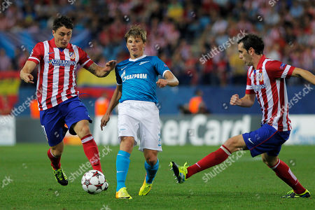 Cristian Rodriguez, Diego Godin, Andrey Arshavin Atletico's Cristian Rodriguez, left, and Diego Godin, right, in action with Zenit St. Petersburg's Andrey Arshavin, centre, during a Group G Champions League soccer match at the Vicente Calderon stadium in Madrid