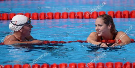 Chloe Sutton of the United States, left, and Hungary's Boglarka Kapas chat after finishing a Women's 1500m freestyle heat at the FINA Swimming World Championships in Barcelona, Spain