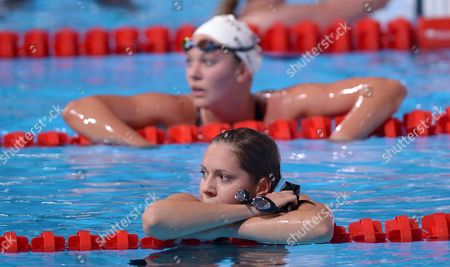 Stock Image of Hungary's Boglarka Kapas, bottom, and Chloe Sutton of the United States rest on lane markers after finishing a Women's 1500m freestyle heat at the FINA Swimming World Championships in Barcelona, Spain