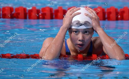 Hong Kong's Stephanie Au Hoi Shun holds her head after finishing a Women's 100m backstroke heat at the FINA Swimming World Championships in Barcelona, Spain