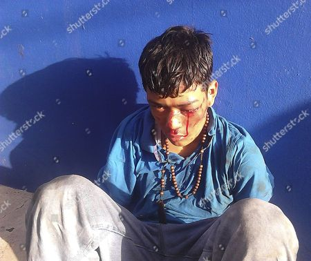 Obtained by the Associated Press, Edwin Mejia sits against a wall with his hands tied behind his back while in police custody in Tegucigalpa, Honduras. Mejia and another minor were detained by police after they allegedly shot and killed a traffic policeman. While under police custody, police beat the two boys in the street and then inside the police station, later sending photos of the boys to the media. One of them died in custody and Mejia was seriously injured