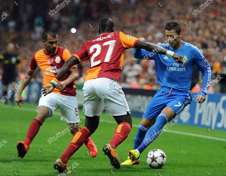 Emmanuel Eboue of Galatasaray, centre, vies for the ball with Real Madrid's Cristian Ronaldo, during their Champions League Group B soccer match, in Istanbul, Turkey