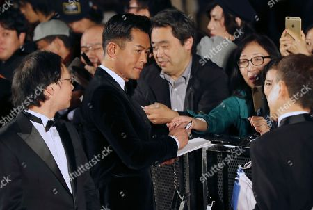 Louis Koo Hong Kong actor Louis Koo, center, gives his autograph to a fan on the red carpet during the opening ceremony of the Tokyo International Film Festival in Tokyo