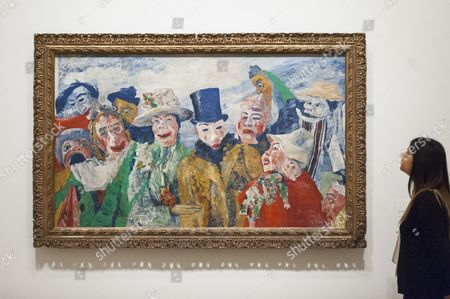 "A staff member views ""The Intrigue, 1890"" at the preview of Intrigue: James Ensor by Luc Tuymans"
